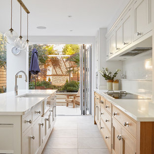 Photo of a classic galley kitchen in London with a belfast sink, shaker cabinets, medium wood cabinets, white splashback, an island, beige floors and white worktops.