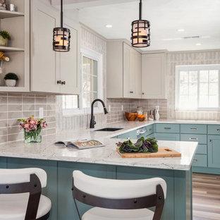 Foto di una cucina ad U tradizionale con lavello sottopiano, ante in stile shaker, ante blu, paraspruzzi grigio, elettrodomestici in acciaio inossidabile, parquet chiaro, penisola, pavimento beige e top bianco