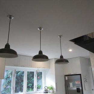 シドニーの中くらいのインダストリアルスタイルのおしゃれなキッチン (ドロップインシンク、シェーカースタイル扉のキャビネット、白いキャビネット、クオーツストーンカウンター、緑のキッチンパネル、サブウェイタイルのキッチンパネル、シルバーの調理設備、セラミックタイルの床、アイランドなし) の写真
