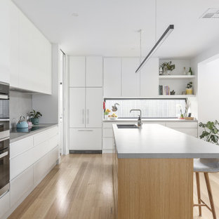 Photo of a contemporary l-shaped kitchen in Melbourne with an undermount sink, flat-panel cabinets, white cabinets, grey splashback, black appliances, light hardwood floors, with island, beige floor and white benchtop.