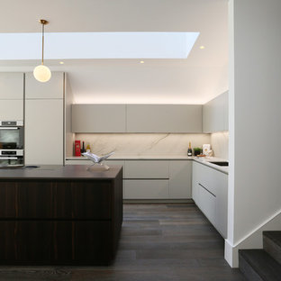 Photo of a medium sized contemporary l-shaped kitchen in London with a submerged sink, grey cabinets, white splashback, marble splashback, stainless steel appliances, dark hardwood flooring, an island, brown floors and white worktops.