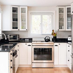 Klassische Küche ohne Insel in U-Form mit Unterbauwaschbecken, Glasfronten, weißen Schränken, Küchengeräten aus Edelstahl, hellem Holzboden und schwarzer Arbeitsplatte in Boston