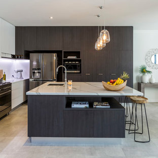 Design ideas for a contemporary l-shaped eat-in kitchen in Gold Coast - Tweed with an undermount sink, flat-panel cabinets, black cabinets, white splashback, stainless steel appliances, with island, grey floor and white benchtop.
