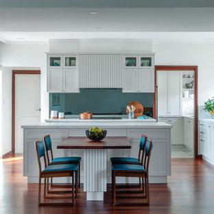 Idéer för stora vintage flerfärgat kök, med en undermonterad diskho, skåp i shakerstil, grå skåp, bänkskiva i koppar, grått stänkskydd, glaspanel som stänkskydd, svarta vitvaror, mörkt trägolv, en köksö och brunt golv