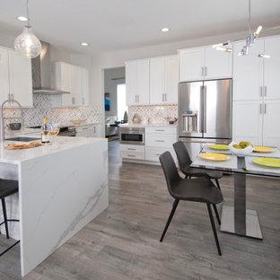 Inspiration för ett mellanstort funkis vit vitt kök, med en undermonterad diskho, skåp i shakerstil, vita skåp, bänkskiva i kvarts, grått stänkskydd, stänkskydd i keramik, rostfria vitvaror, laminatgolv och grått golv