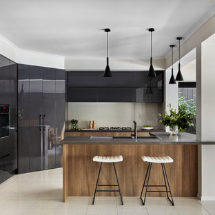 Contemporary eat-in kitchen in Melbourne with flat-panel cabinets, grey cabinets, beige splashback, glass sheet splashback, stainless steel appliances, with island, beige floor and grey benchtop.