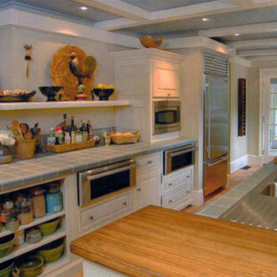Large country l-shaped separate kitchen in New York with a double-bowl sink, raised-panel cabinets, white cabinets, tile benchtops, stainless steel appliances, light hardwood floors, brown floor and turquoise benchtop.