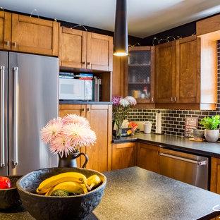 モントリオールの中くらいのインダストリアルスタイルのおしゃれなキッチン (アンダーカウンターシンク、シェーカースタイル扉のキャビネット、中間色木目調キャビネット、御影石カウンター、黒いキッチンパネル、磁器タイルのキッチンパネル、シルバーの調理設備、磁器タイルの床) の写真