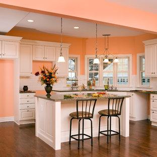 デトロイトの中サイズのヴィクトリアン調のおしゃれなキッチン (ドロップインシンク、レイズドパネル扉のキャビネット、白いキャビネット、御影石カウンター、黄色いキッチンパネル、セラミックタイルのキッチンパネル、シルバーの調理設備の、濃色無垢フローリング、茶色い床、グレーのキッチンカウンター) の写真