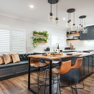 Transitional eat-in kitchen in Perth with shaker cabinets, black cabinets, white splashback, stainless steel appliances, medium hardwood floors, with island, brown floor and white benchtop.
