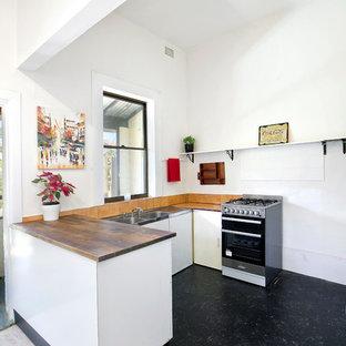 シドニーのヴィクトリアン調のおしゃれなコの字型キッチン (ダブルシンク、インセット扉のキャビネット、白いキャビネット、木材カウンター、白いキッチンパネル、シルバーの調理設備の、ラミネートの床、アイランドなし、黒い床、茶色いキッチンカウンター) の写真