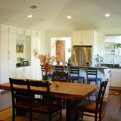 Example of a trendy eat-in kitchen design in Austin with white cabinets and stainless steel appliances