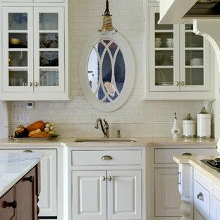Foto på ett vintage kök, med en undermonterad diskho, luckor med upphöjd panel, vita skåp, vitt stänkskydd och stänkskydd i tunnelbanekakel