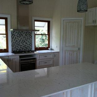 Diseño de cocina en U, rural, de tamaño medio, con suelo de madera clara, fregadero bajoencimera, salpicadero con mosaicos de azulejos, electrodomésticos de acero inoxidable y suelo violeta
