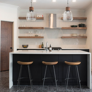 Design ideas for a contemporary galley kitchen in Edmonton with an integrated sink, flat-panel cabinets, black cabinets, white splashback, with island, black floor and white benchtop.