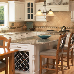 Inspiration for a mid-sized traditional l-shaped eat-in kitchen in New York with an undermount sink, louvered cabinets, white cabinets, granite benchtops, beige splashback, ceramic splashback, stainless steel appliances, medium hardwood floors, with island and brown floor.
