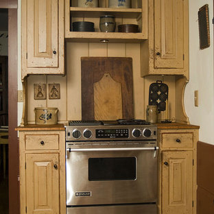 Example of a classic kitchen design in Cincinnati with wood countertops and distressed cabinets
