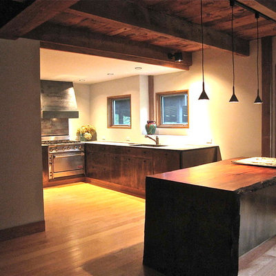 Example of a large mountain style l-shaped medium tone wood floor eat-in kitchen design in New York with a single-bowl sink, flat-panel cabinets, granite countertops, an island, stainless steel appliances and white cabinets