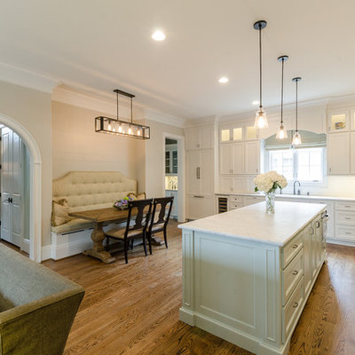 Example of a classic l-shaped eat-in kitchen design in Birmingham with recessed-panel cabinets, white cabinets, white backsplash and stainless steel appliances