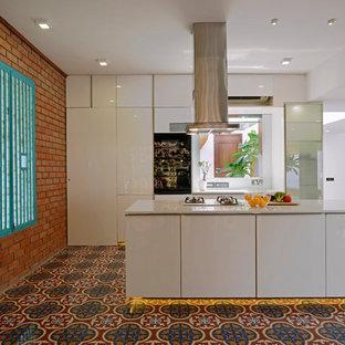 Diseño de cocina de galera, exótica, abierta, con armarios con paneles lisos, puertas de armario blancas, electrodomésticos de acero inoxidable, suelo de baldosas de cerámica, una isla y suelo multicolor