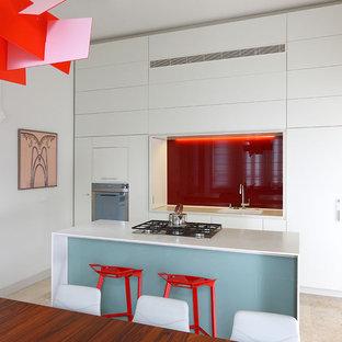Diseño de cocina comedor de galera, moderna, pequeña, con armarios con paneles lisos, puertas de armario blancas, encimera de acrílico, salpicadero rojo, salpicadero de vidrio templado, electrodomésticos de acero inoxidable, fregadero encastrado, suelo de piedra caliza y una isla