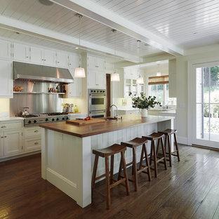 Bild på ett vintage kök, med rostfria vitvaror, träbänkskiva, vita skåp, skåp i shakerstil, stänkskydd med metallisk yta, stänkskydd i metallkakel, en undermonterad diskho, en köksö och mörkt trägolv