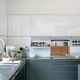This is an example of a large contemporary u-shaped eat-in kitchen in Little Rock with a double-bowl sink, stainless steel benchtops, white splashback, with island, flat-panel cabinets, glass sheet splashback, stainless steel appliances, porcelain floors and grey cabinets.