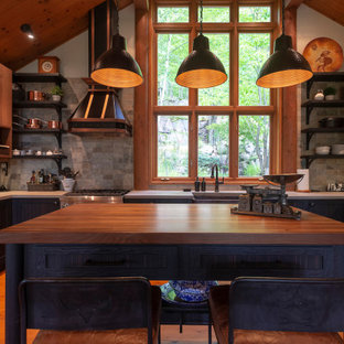 Mid-sized country u-shaped eat-in kitchen in Montreal with a farmhouse sink, flat-panel cabinets, medium wood cabinets, concrete benchtops, grey splashback, stone tile splashback, stainless steel appliances, medium hardwood floors, with island, orange floor and grey benchtop.