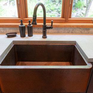 モントリオールの中サイズのラスティックスタイルのおしゃれなキッチン (エプロンフロントシンク、フラットパネル扉のキャビネット、中間色木目調キャビネット、コンクリートカウンター、グレーのキッチンパネル、石タイルのキッチンパネル、シルバーの調理設備、無垢フローリング、オレンジの床、グレーのキッチンカウンター) の写真