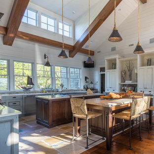 Design ideas for a large beach style u-shaped open plan kitchen in Charleston with recessed-panel cabinets, distressed cabinets, granite benchtops, stainless steel appliances, ceramic floors and multiple islands.