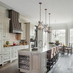 Esempio di una cucina parallela country con lavello stile country, ante con bugna sagomata, ante bianche, paraspruzzi bianco, elettrodomestici in acciaio inossidabile, parquet scuro, isola e pavimento marrone