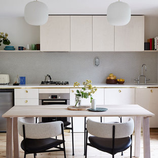 This is an example of a contemporary single-wall eat-in kitchen in Melbourne with an undermount sink, flat-panel cabinets, light wood cabinets, stainless steel appliances, light hardwood floors and no island.