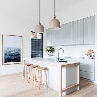 Design ideas for a modern galley kitchen in Melbourne with an undermount sink, flat-panel cabinets, grey cabinets, white splashback, light hardwood floors, with island, beige floor and white benchtop.