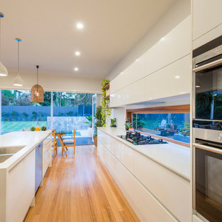 Design ideas for a contemporary galley eat-in kitchen in Brisbane with a double-bowl sink, flat-panel cabinets, white cabinets, stainless steel appliances, light hardwood floors and an island.