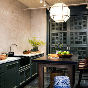 Inspiration pour une cuisine asiatique avec un évier de ferme, un placard avec porte à panneau encastré, des portes de placards vertess, une crédence beige et un îlot central.