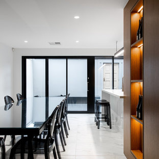 Design ideas for a mid-sized contemporary eat-in kitchen in Adelaide with brown cabinets, solid surface benchtops, grey splashback, ceramic splashback, black appliances, marble floors, with island, white benchtop and grey floor.
