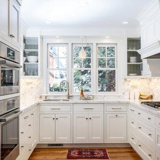ボストンのトランジショナルスタイルのおしゃれなコの字型キッチン (アンダーカウンターシンク、シェーカースタイル扉のキャビネット、白いキャビネット、白いキッチンパネル、シルバーの調理設備、無垢フローリング、茶色い床、白いキッチンカウンター) の写真
