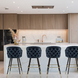 Design ideas for a contemporary galley kitchen in London with a submerged sink, flat-panel cabinets, medium wood cabinets, stainless steel appliances, an island, grey floors and white worktops.