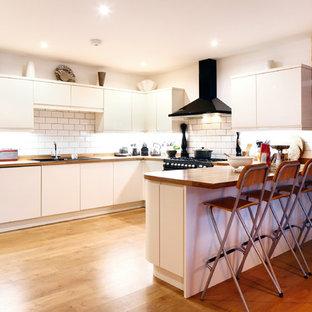 サセックスの巨大な北欧スタイルのおしゃれなキッチン (ドロップインシンク、フラットパネル扉のキャビネット、白いキャビネット、木材カウンター、白いキッチンパネル、サブウェイタイルのキッチンパネル、黒い調理設備、無垢フローリング) の写真