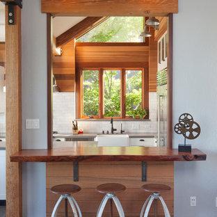 サンフランシスコのカントリー風おしゃれなダイニングキッチン (エプロンフロントシンク、木材カウンター、濃色無垢フローリング、赤い床) の写真