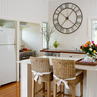 Beach style u-shaped kitchen in Brisbane with a drop-in sink, recessed-panel cabinets, white cabinets, white splashback, stainless steel appliances, medium hardwood floors, with island, brown floor and white benchtop.