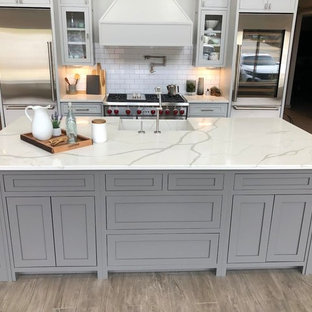 Design ideas for a mid-sized country u-shaped eat-in kitchen in Atlanta with an integrated sink, recessed-panel cabinets, grey cabinets, quartzite benchtops, white splashback, subway tile splashback, stainless steel appliances, with island and white benchtop.