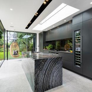 ロンドンのコンテンポラリースタイルのおしゃれなキッチン (アンダーカウンターシンク、フラットパネル扉のキャビネット、黒いキャビネット、黒いキッチンパネル、ガラス板のキッチンパネル、シルバーの調理設備の、コンクリートの床) の写真