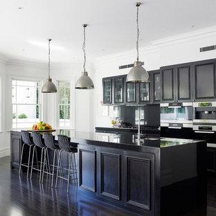Foto de cocina de galera, clásica, con armarios con paneles empotrados, puertas de armario de madera en tonos medios, electrodomésticos de acero inoxidable, suelo de madera oscura y una isla