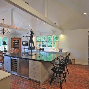 ボルチモアの大きいトラディショナルスタイルのおしゃれなキッチン (アンダーカウンターシンク、シェーカースタイル扉のキャビネット、黒いキャビネット、クオーツストーンカウンター、シルバーの調理設備の、レンガの床、赤い床) の写真