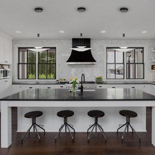 Foto di una cucina abitabile moderna di medie dimensioni con lavello da incasso, ante bianche, top in onice, paraspruzzi grigio, paraspruzzi con piastrelle a mosaico, elettrodomestici neri, pavimento in compensato, isola, pavimento marrone e top nero
