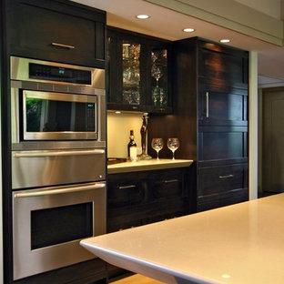 バンクーバーの大きいアジアンスタイルのおしゃれなキッチン (シェーカースタイル扉のキャビネット、濃色木目調キャビネット、シルバーの調理設備の) の写真