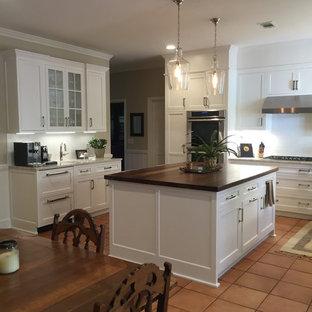サンディエゴの中サイズのコンテンポラリースタイルのおしゃれなキッチン (アンダーカウンターシンク、シェーカースタイル扉のキャビネット、白いキャビネット、白いキッチンパネル、サブウェイタイルのキッチンパネル、木材カウンター、シルバーの調理設備の、テラコッタタイルの床、赤い床) の写真