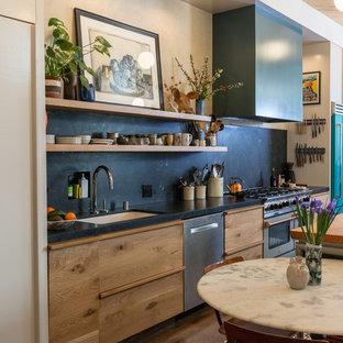 Идея дизайна: параллельная кухня-гостиная в стиле фьюжн с врезной раковиной, плоскими фасадами, фасадами цвета дерева среднего тона, столешницей из дерева, черным фартуком, фартуком из каменной плиты, цветной техникой, паркетным полом среднего тона, островом и коричневым полом