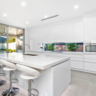 Photo of a contemporary kitchen in Perth with an undermount sink, flat-panel cabinets, white cabinets, window splashback, white appliances, with island, grey floor and white benchtop.
